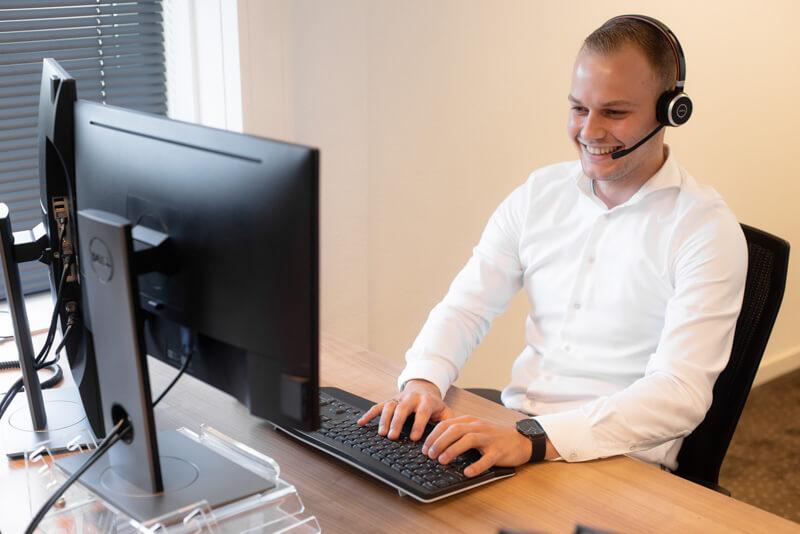 Medewerker met headset achter computer
